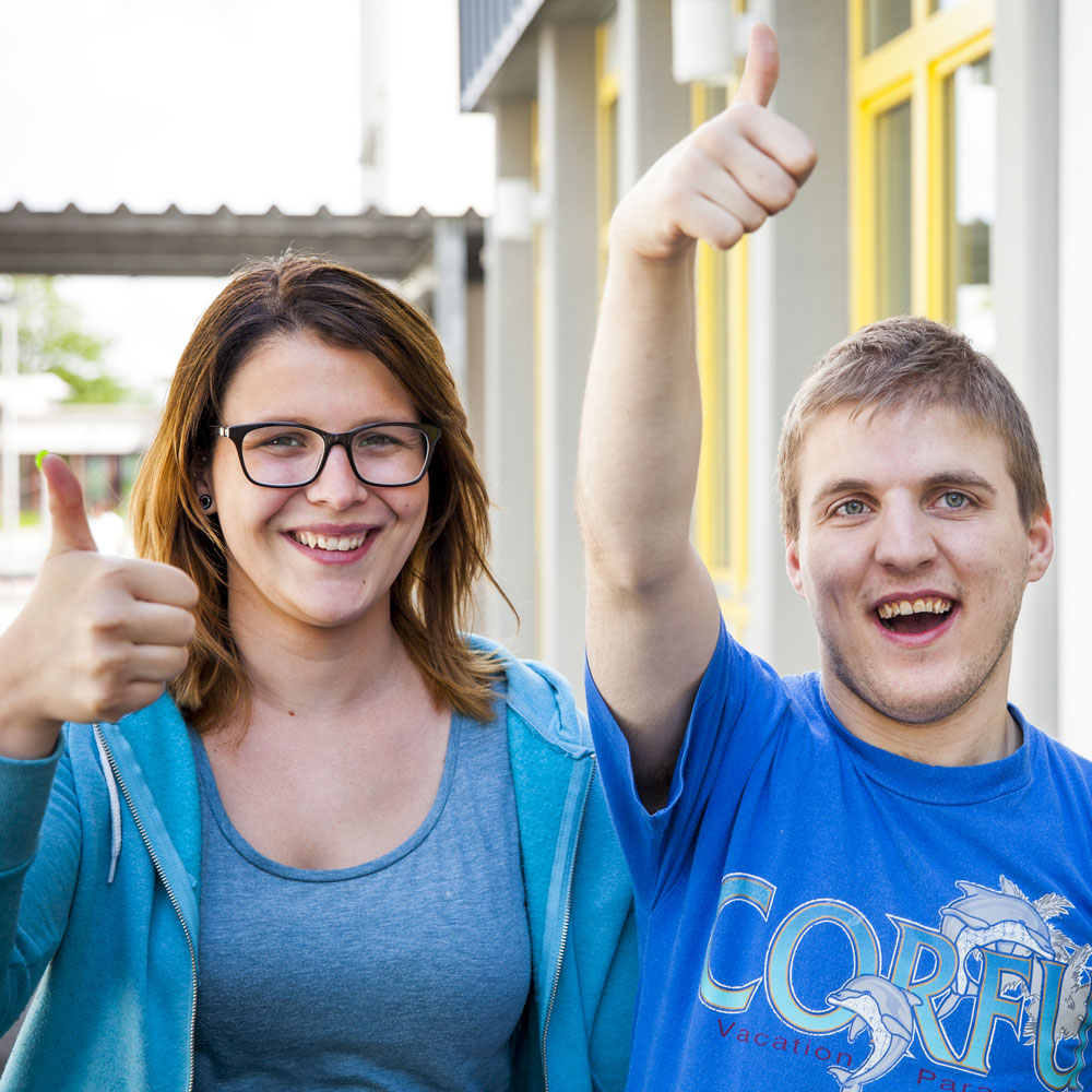Zwei junge Menschen zeigen den Daumen hoch.