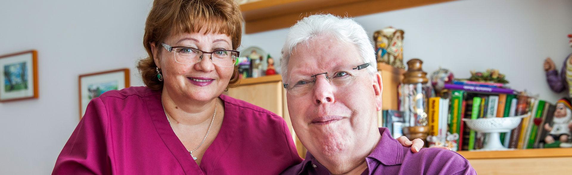 Pflegerin und Senior lächeln