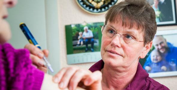 Eine Pflegerin gibt eine Spritze